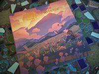 Das Cover von Wanderhome, auf dem man einen Dachs-Hirtten auf einer Wiese sitzen sieht, der eine Herde Motten beobachtet.